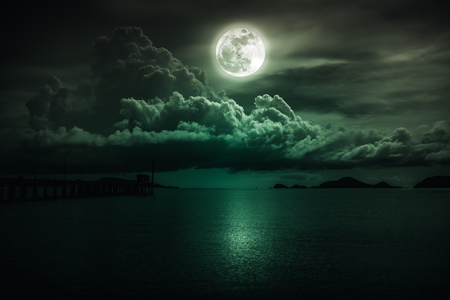 Beautiful landscape view of the sea. Colorful emerald sky with clouds and bright full moon on seascape to night. Serenity nature background, outdoor at nighttime. The moon taken with my own camera. Stock Photo