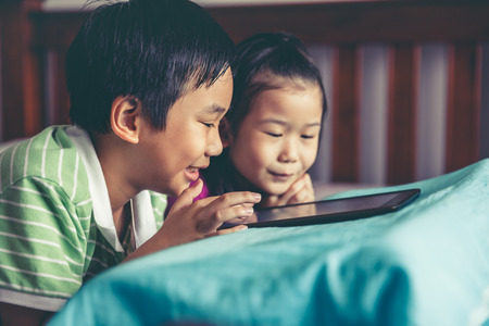Chinese boy and his pretty younger sister smiling and lying prone on bed. Asian children playing game on digital tablet together. Conceptual about loving of sibling. Vintage film filter effect. Stockfoto