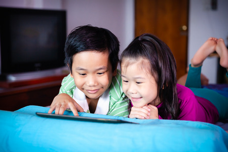 Asian children watching digital tablet for learning together. Chinese boy and his younger sister smiling and lying prone on bed. Conceptual about using E-learning technologies for educational at home.