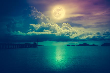 Beautiful landscape view of the sea. Colorful sky with clouds and bright full moon on seascape to night. Serenity nature background, outdoor at nighttime. Cross process. The moon taken with my own camera. Stock Photo