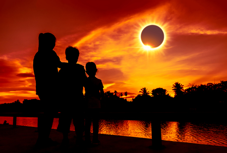 Amazing scientific natural phenomenon. The Moon covering the Sun. Silhouette of mother ans children looking at total solar eclipse with diamond ring effect on sky. Happy family spending time together.