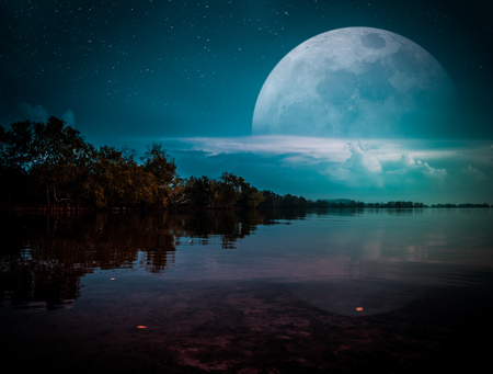 Photo Manipulation. Landscape of night sky with many stars. Beautiful super moon behind partial cloudy above silhouettes of trees, lake area. Serenity nature background. The moon taken with my camera. Reklamní fotografie