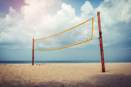 Torn volleyball net on an empty beach with cloudy blue sky. Outdoor at the daytime with bright sunny on summer day. Sport concepts. Vintage effect tone.