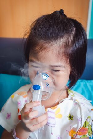 Sad asian child holds a mask vapor inhaler for treatment of asthma. Breathing through a steam nebulizer.Illness girl admitted in hospital.