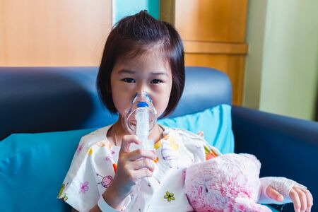 Sad asian child holds a mask vapor inhaler for treatment of asthma and on sickbed in hospital while saline intravenous (IV) on hand. Breathing through a steam nebulizer.