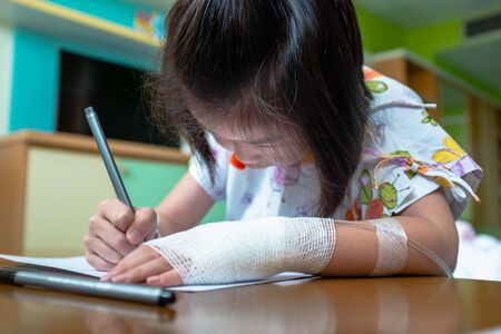 Illness girl admitted in hospital while saline intravenous (IV) on hand. Girl Drawing on a white paper.