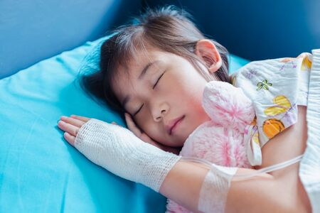 Closeup of illness asian child admitted in hospital with saline intravenous (IV) on hand. Girl sleeping at comfortable equipped hospital room. Health care stories. Stock Photo