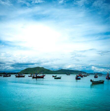 Schöne Natur-Meereslandschaft. Das ruhige Meer mit Bergen tagsüber. Viele Fischerboote schwimmen in der Bucht des Meeres im Süden Thailands.