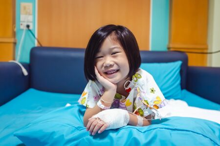 Illness asian child smiling happily and looking at camera. Girl admitted in hospital while saline intravenous (IV) on hand and propping up her face. Health care stories.