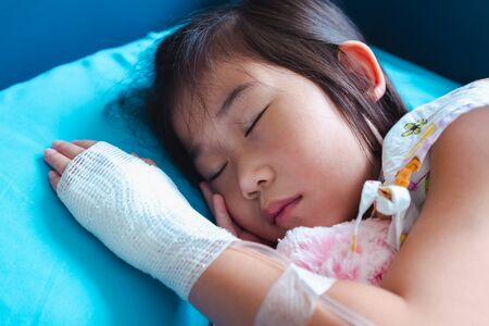 Closeup of illness asian child admitted in hospital with saline intravenous (IV) on hand. Girl sleeping at comfortable equipped hospital room. Health care stories. 版權商用圖片