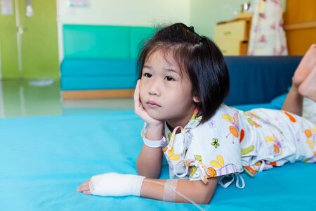 Illness asian child admitted in hospital while saline intravenous (IV) on hand. Unhappy girl feeling sad, bored, kid emotion. Concept for depression stress or frustration. Health care stories. Stock Photo