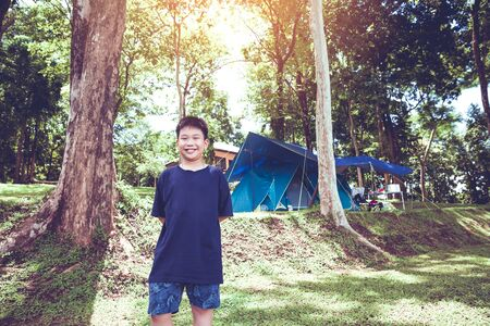 Cute little asian boy under big tree outdoor in the park. camping tent on background.