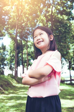 Portrait of a smiling little asian girl in the park. Stock Photo
