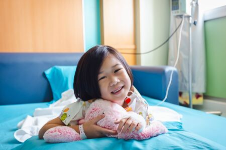 Illness asian child smiling happily and looking at camera. Girl admitted in hospital while saline intravenous (IV) on hand. Health care stories. Stock Photo