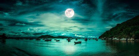 Beautiful panorama nature landscape. Beach by the sea with mountains and full moon at nighttime.Many fishing boats Floating in the bay of the sea in southern Thailand. The moon taken with my camera.