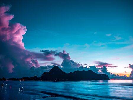 Fantastic morning blue sea glowing by sunlight.Beach by the sea with mountains in the bay of the sea in southern Thailand. Stock Photo