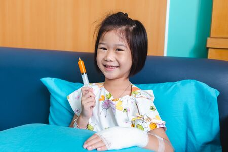 Close up of illness asian child admitted in hospital with saline intravenous (IV) on hand. Girl feeling happy while taking medicine syrup, facial expression. Health care stories.
