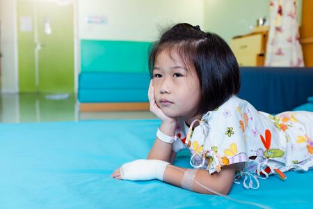 Illness asian child admitted in hospital while saline intravenous (IV) on hand. Unhappy girl feeling sad, bored, kid emotion. Concept for depression stress or frustration. Health care stories.