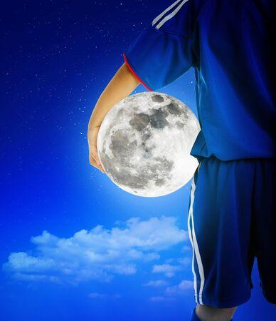 Vista posteriore del calciatore giovanile in uniforme blu che tiene la luna piena luminosa. Archivio Fotografico