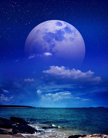 Landscape view of the sea with many stars. Beautiful sky with super moon behind partial cloudy. Serenity nature background. Stock Photo