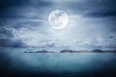 Landscape view of the sea with many stars. Beautiful sky with super moon over seascape. Serenity nature background.