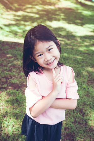 Portrait of a smiling little asian girl on green grass in the park.