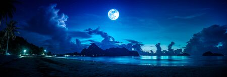 Beautiful panorama view of the sea. Colorful blue sky with cloud and bright full moon on seascape to night. Serenity nature background outdoor at nighttime. The moon taken with my own camera. Stock Photo