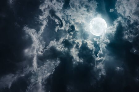 Landscape of sky with dark clouds at nighttime. Beautiful full moon behind cloudy with moonlight, serenity nature background. The moon taken with my own camera.