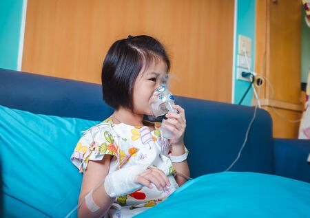 Sad asian child holds a mask vapor inhaler for treatment of asthma. Breathing through a steam nebulizer.Illness girl admitted in hospital while saline intravenous (IV) on hand.