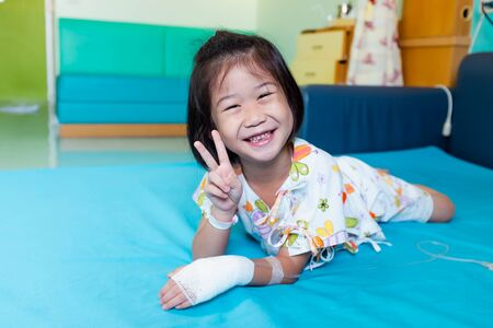 Illness asian child smiling happily and showing v-sign. Girl admitted in hospital while saline intravenous (IV) on hand. Health care stories.