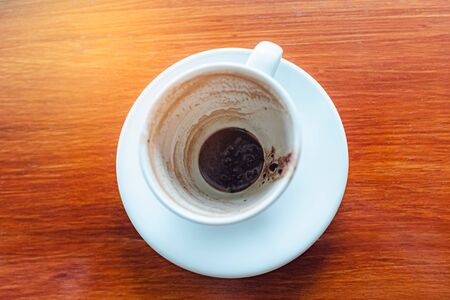 Top view of empty hot coffee cup after drink on wood table background.  Stock Photo