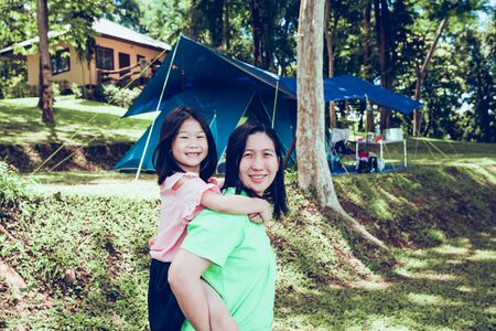 Cute asian daughter on a piggy back ride with her mother in the national park with camping tent on background.