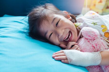 Close up. Illness asian child smiling happily and looking at camera. Girl admitted in hospital while saline intravenous (IV) on hand. Health care stories.