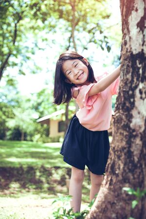 Cute little asian girl under big tree outdoor in the park.