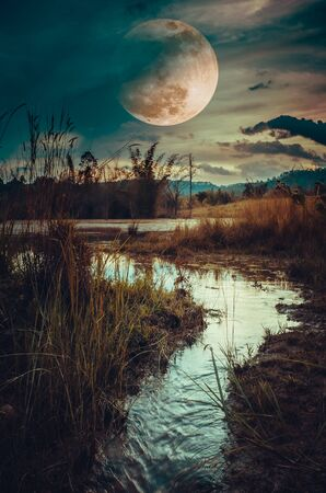 Landscape at night time in the forest lake and darkness sky super moon Stock Photo