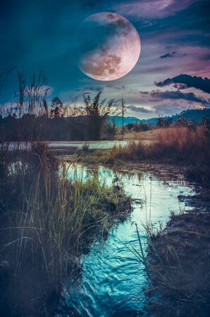 Landscape at night time in the forest lake with fogy and darkness sky super moon Stock Photo