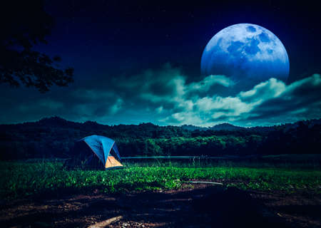 Great view of camping tent near lake at night with many stars. Beautiful full moon and cloudy with mountain range in the background. Serenity nature background. The concept of travel, tourism, camping Stock Photo