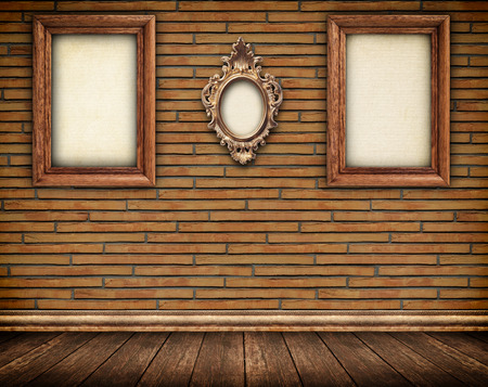 skirting: Three old frames on brick wall and wooden floor with skirting board.