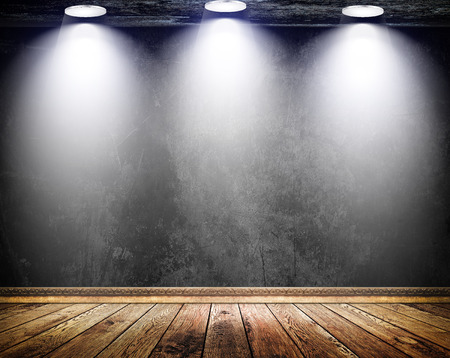 plinth: Old black concrete wall with three light sources  and old wooden floor with decorative wooden plinth. Stock Photo