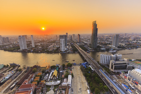 Cityscape of River in Bangkok city with high office building at sunset