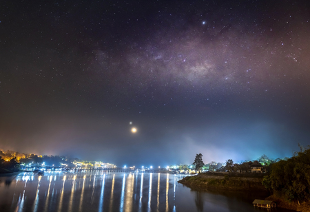 The Milky Way is above the old wooden bridge (Mon Bridge), Kanchanaburi province, Thailand. 免版税图像