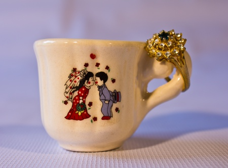 Cup has a little gift and wedding couples stuck. photo