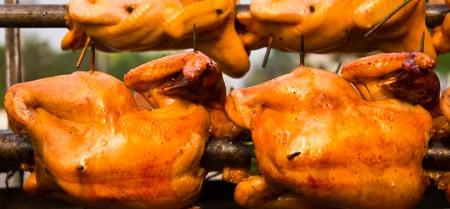 Rotating roast chicken, but not cooked. Stock Photo