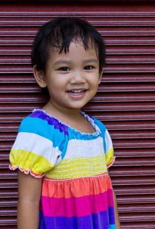 Thai children standing next to a wood door brown looking for something. Stock Photo - 10875118