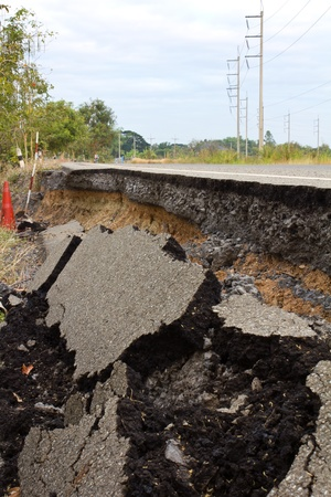 Side along the asphalt road collapsed because of erosion.