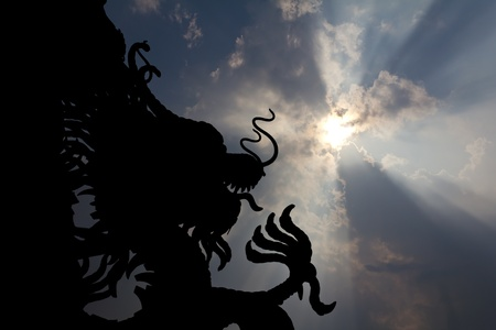 Large statues of Dragon black silhouette in sky prominently. photo