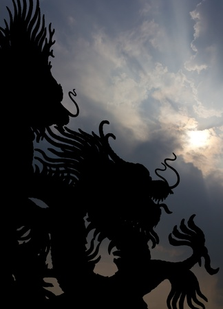 Large statues of Dragon black silhouette in sky prominently. Stock Photo - 11893423