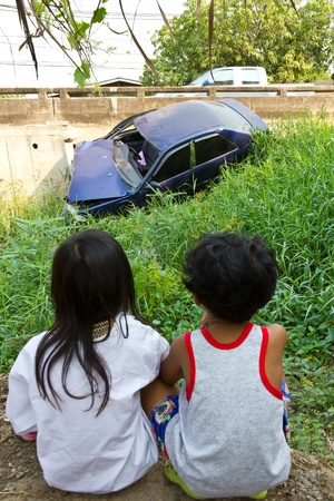 Children watching a car accident, car drove into some bushes.  Stock Photo