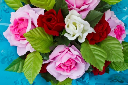 Artificial colored roses on a blue background Stock Photo - 12864706