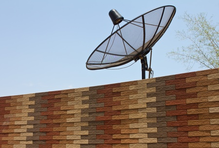 Black satellite dish above the modern brick walls  photo